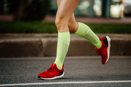women feet runner in green compression socks and red running shoes