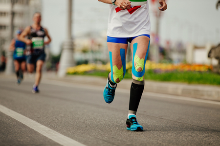 082dd36c2 legs woman runner in compression socks and kinesio tape on knees Stock Photo