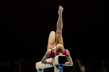 balance beam performing female gymnast at gymnastics championship 免版税图像