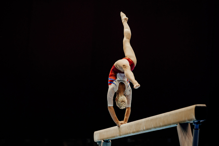 poutre d'équilibre handstand gymnaste féminine sur fond noir Banque d'images