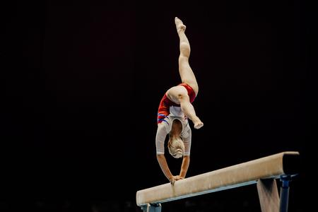 Viga de equilibrio handstand gimnasta femenina sobre fondo negro Foto de archivo