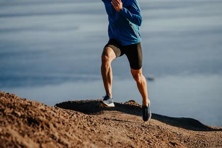 man runner run steep mountain on background of sea