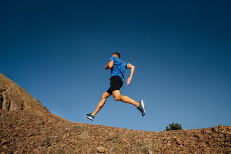 athlete runner running uphill mountain trail