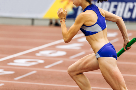 woman runner running relay race with baton in hand