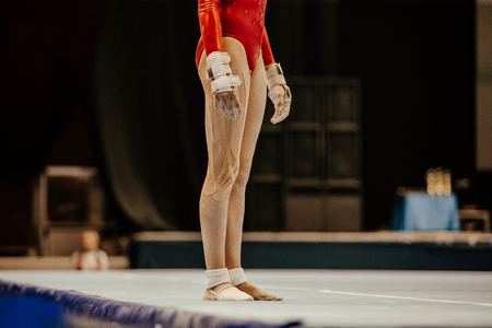 woman gymnast preparing for exercise uneven bars in artistic gymnastics