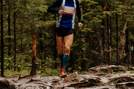 male athlete runner running forest trail splashes of water and mud