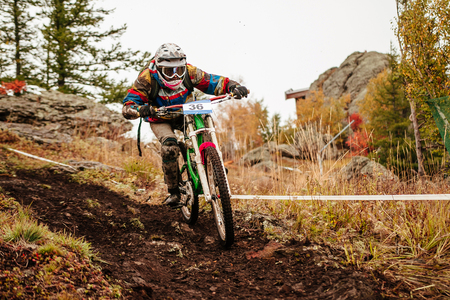 downhill mountain biking rider riding on dirty trail