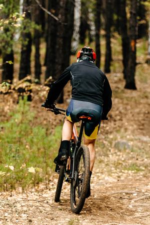 indietro ciclista maschio in mountain bike in sella a un sentiero nel bosco