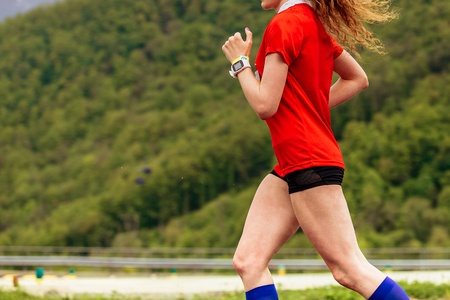 red-haired woman runner with timer on his hand running on background of mountains with forest