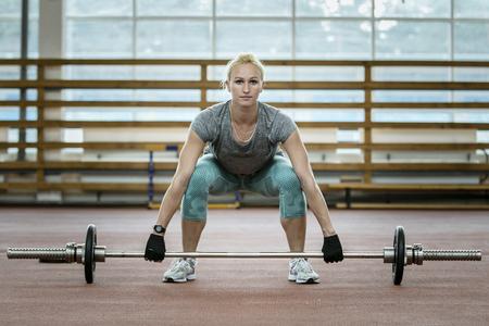 female athlete doing exercise deadlift barbell in gym