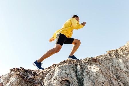 man climb uphill mountain in yellow jacket background sky