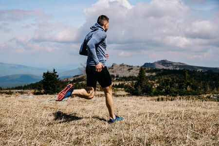 Hombre corredor corriendo pista de maratón de montaña sobre hierba amarilla Foto de archivo