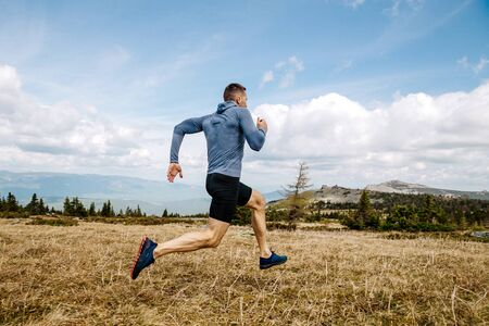 male runner cross country running on mountain trail in summer outdoor Banco de Imagens