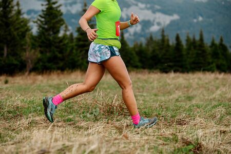 woman athlete runner running mountain trail marathon race Banco de Imagens