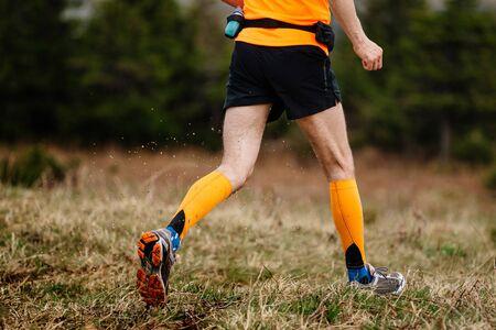 legs runner man in orange compression socks running on trail water spray