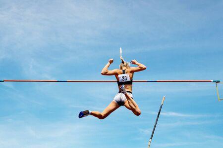 Stabhochsprung Frau Voltigierer erfolgreicher Versuch, Hintergrund im blauen Himmel zu fliegen