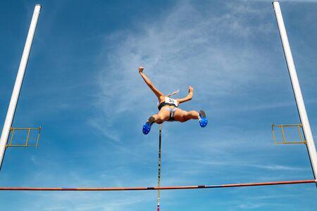 Stabhochsprung Sportlerin klopft Bar, um Hintergrund blauer Himmel zu fliegen Standard-Bild