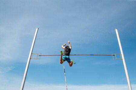 Stabhochsprung Mann Athlet klopft Bar, um Hintergrund blauer Himmel zu fliegen Standard-Bild