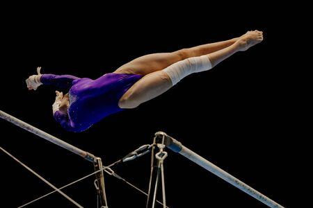 Performance de gymnaste femme sur la gymnastique aux barres asymétriques sur fond noir