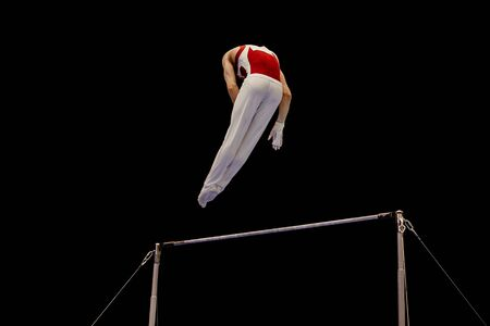 man gymnast performing on horizontal bar on background black
