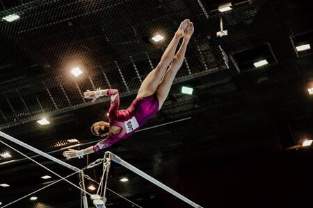 female gymnast leaps to higher bar gymnastics on black background and bright lamps