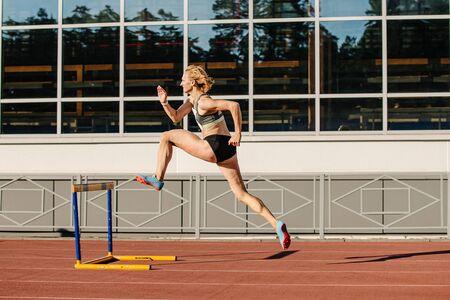 female athlete run 400 meters hurdles in athletics at stadium