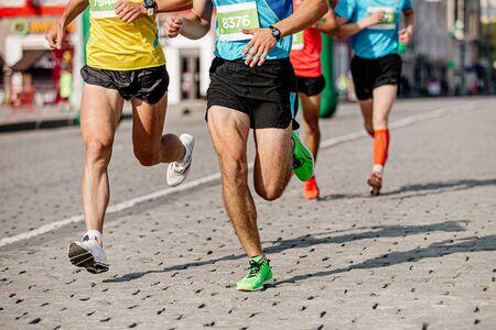 group of runners athletes run on cobblestones city marathon
