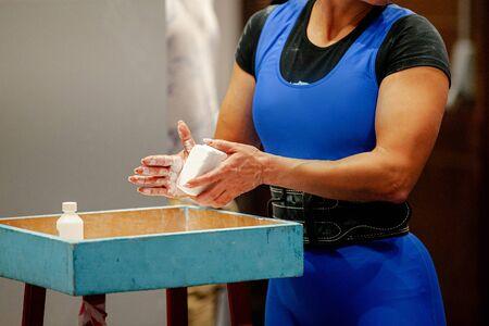 women powerlifter apply gym chalk on hands before attempting in deadlift  Stok Fotoğraf