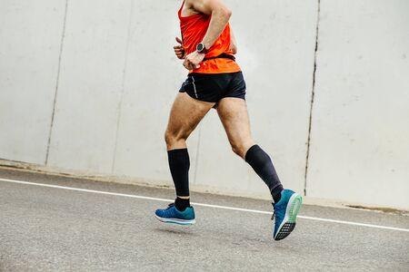 corridore degli uomini in calze a compressione che corrono in salita sullo sfondo del muro di cemento
