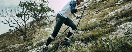 man runner with trekking poles climbing uphill mountain marathon. panoramic banner concept copy space