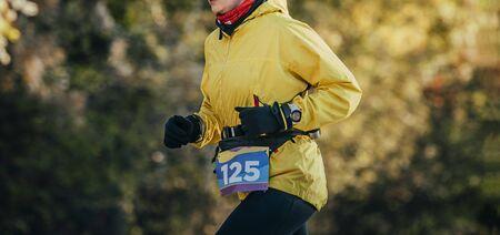 woman runner in yellow jacket run fall marathon Reklamní fotografie