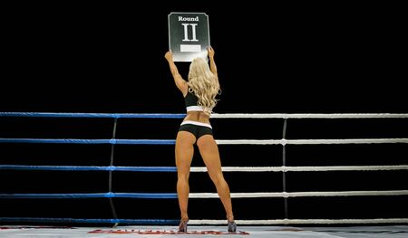 back boxing ring girl carrying sign that displays number of upcoming round