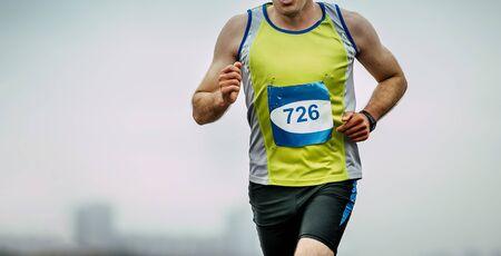 male athlete runner running marathon on light background