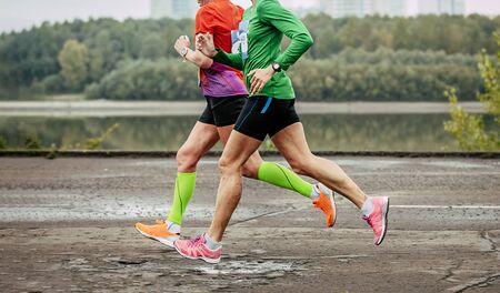 two female athletes runners run marathon on river embankment Reklamní fotografie