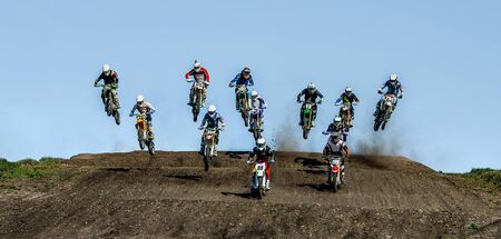 group athletes motocross riders coming off jump Imagens