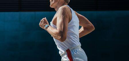 old male runner running marathon on dark background