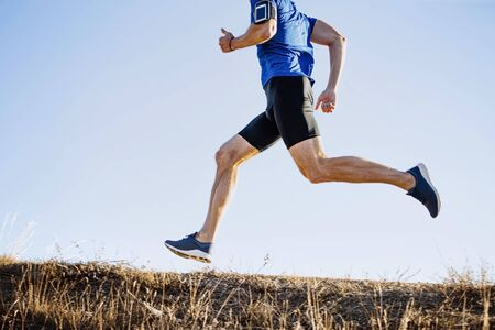 male runner running mountain trail on blue sky background Stock Photo