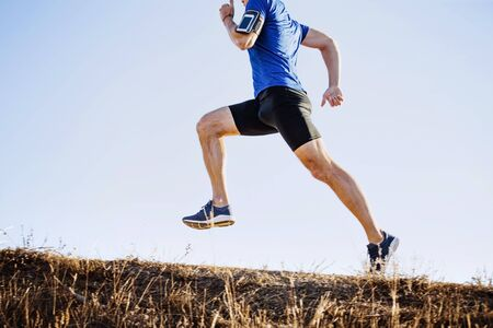 male runner running uphill, armband holder with mobile phone