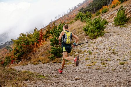 male athlete with backpack and trekking poles running mountain trail