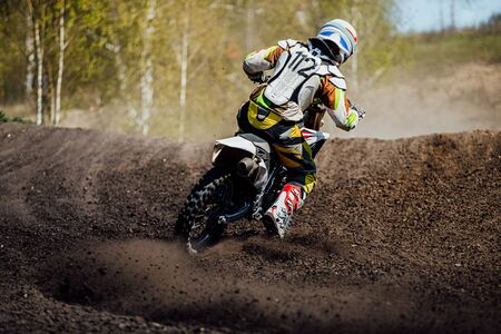 back motocross rider ground and dust from under rear wheel Imagens