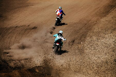 back two motocross riders in race ground track