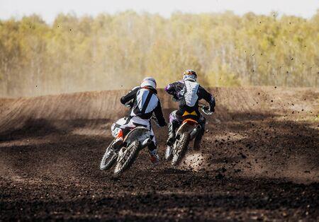 motocross racers on race track splashing mud from under wheels