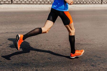 legs male runner in compression socks run asphalt road