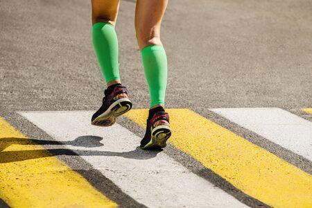 legs female runner in compression socks running on pedestrian crossing