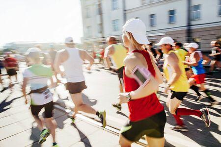 large group runners run marathon on city in morning sunlight