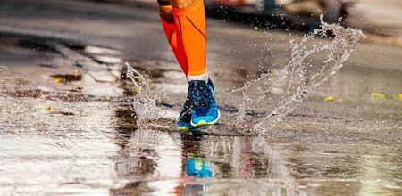 legs runner in orange compression socks run puddle, splashes of water