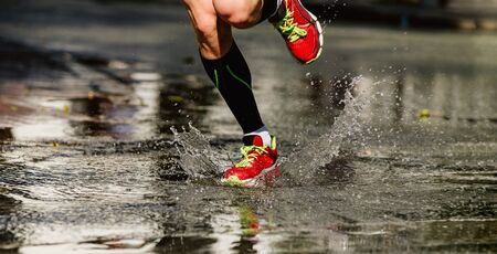 feet runner athlete run puddle on road, water splash Reklamní fotografie