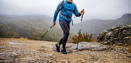man with trekking poles walk mountain trail in rainy autumn weather