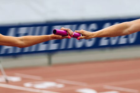 relay race running women 4Ñ…100 metres passing of baton. in background banner Athletics 2020