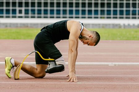athlete runner with prosthetic legs start sprint in track stadium Imagens